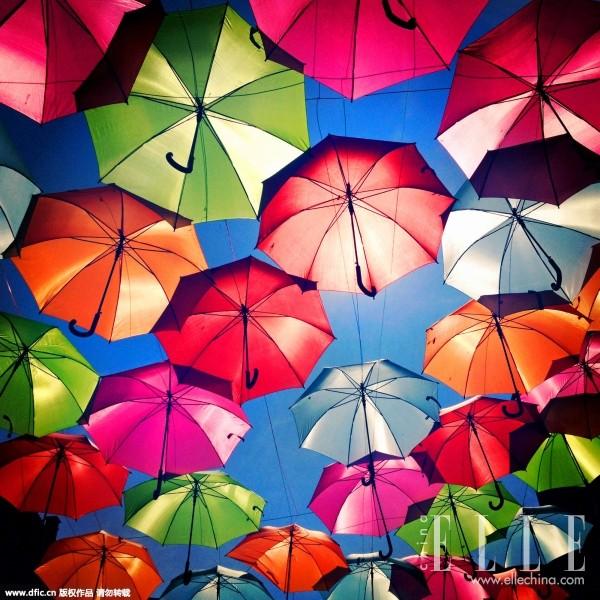 这其实是葡萄牙的一处街头艺术装置,各色七彩雨伞遮蔽了整条